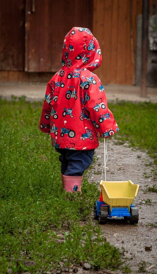 Περίπατοι για τα παιδιά στο καθαρό αέρα Ένα παιδί στέκεται στο υγρό ίχνος και κρατά το αυτοκίνητο παιχνιδιών σχοινιών στοκ εικόνες