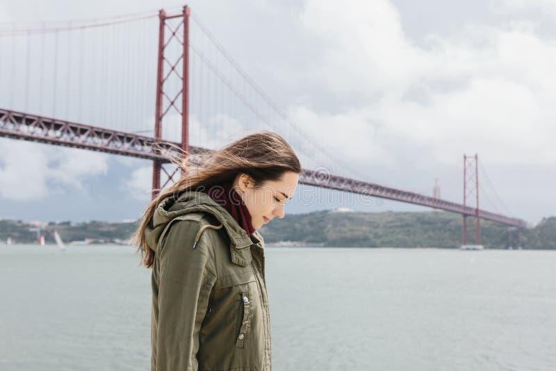 Περίπατοι όμορφοι κοριτσιών μόνο κατά μήκος της ακτής κοντά στη γέφυρα στη Λισσαβώνα στοκ φωτογραφία με δικαίωμα ελεύθερης χρήσης