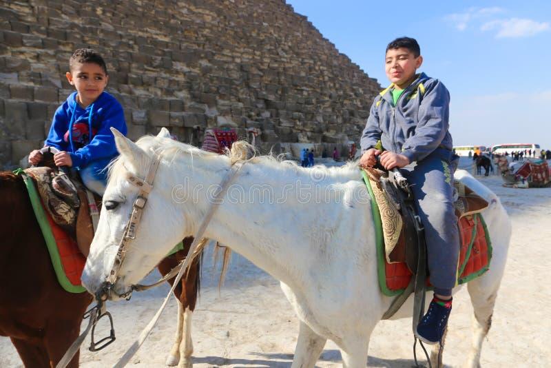 Περίπατος παιδιών στα άλογα στις πυραμίδες Αίγυπτος στοκ φωτογραφίες
