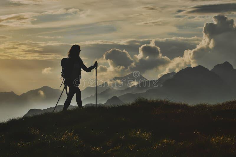 Περίπατος στη μοναξιά στις Άλπεις Μια γυναίκα επάνω με το υπόβαθρο στοκ εικόνες