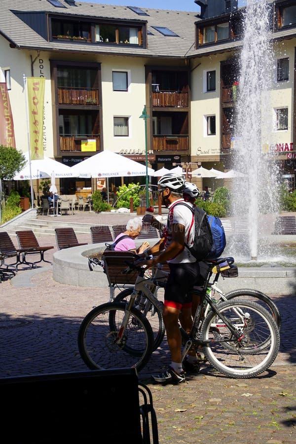 Περίπατος Bicyclists μέσω της πλατείας της πόλης στοκ εικόνες