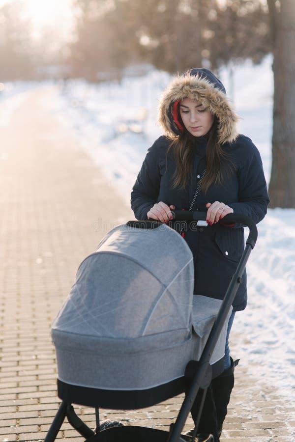 Περίπατος Mom με το μωρό στο καροτσάκι χιονώδης χειμώνας δέντρων πάρκων φύσης Ιανουαρίου παγετού ημέρας Ευτυχής γυναίκα με το μωρ στοκ εικόνα με δικαίωμα ελεύθερης χρήσης