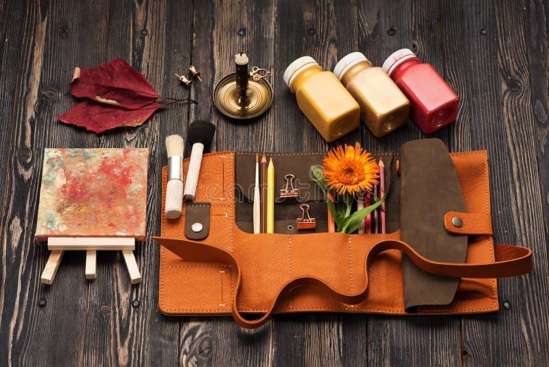 Περίπτωση δέρματος με τα χρωματισμένα μολύβια, τις βούρτσες και το χρώμα για το σχέδιο στοκ φωτογραφία