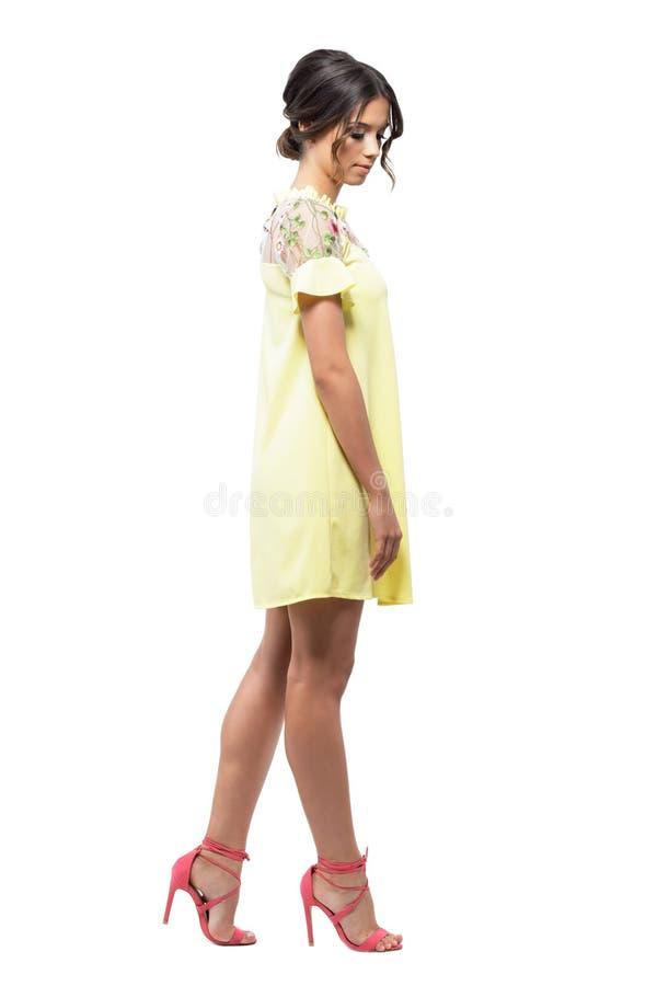 Περίπλοκη θηλυκή νέα γυναίκα στο κοντό κίτρινο φόρεμα βραδιού που περπατά και που κοιτάζει κάτω στοκ εικόνες
