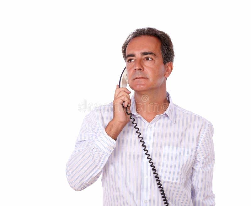 Περίπλοκο ανώτερο αρσενικό που μιλά στο τηλέφωνο στοκ εικόνες