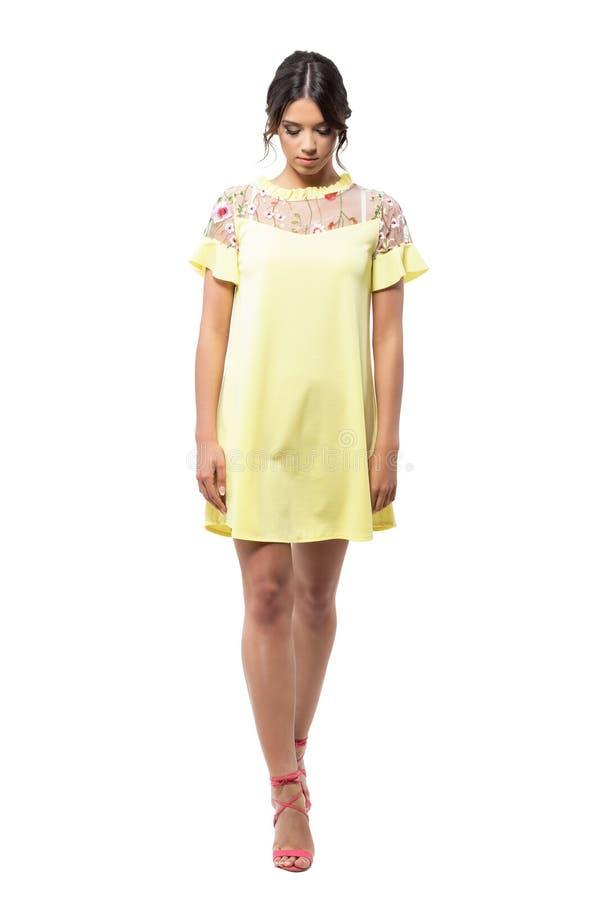 Περίπλοκο νέο πρότυπο μόδας διαδρόμων στο κίτρινο φόρεμα που περπατά και που κοιτάζει κάτω στοκ εικόνες