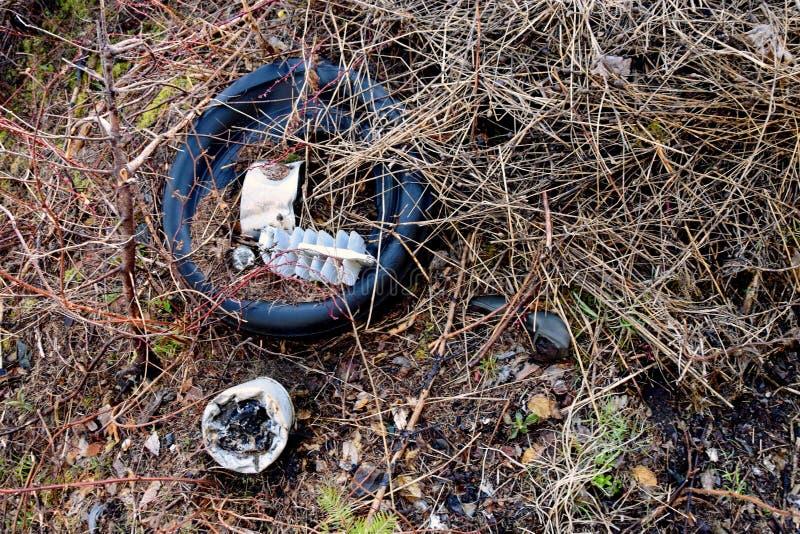 Περιβαλλοντικά ρόδες ρύπανσης και απορρίμματα οικιακών απορριμάτων στη φύση στοκ εικόνες