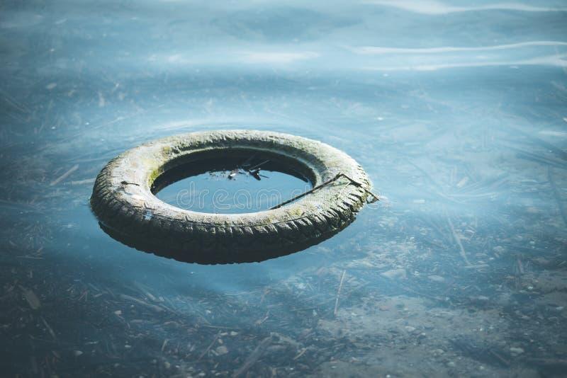 Περιβαλλοντική ρύπανση: το παλαιό ελαστικό αυτοκινήτου βρίσκεται στο νερό, ακτή στοκ φωτογραφίες