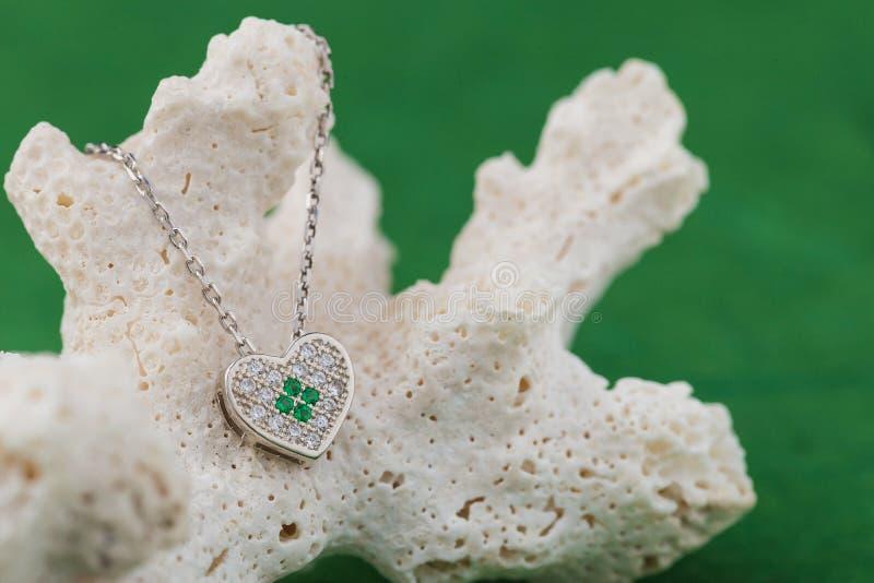 Περιδέραιο καρδιών πολυτέλειας με τα κρύσταλλα στο κοράλλι ενάντια στο πράσινο backg στοκ φωτογραφία