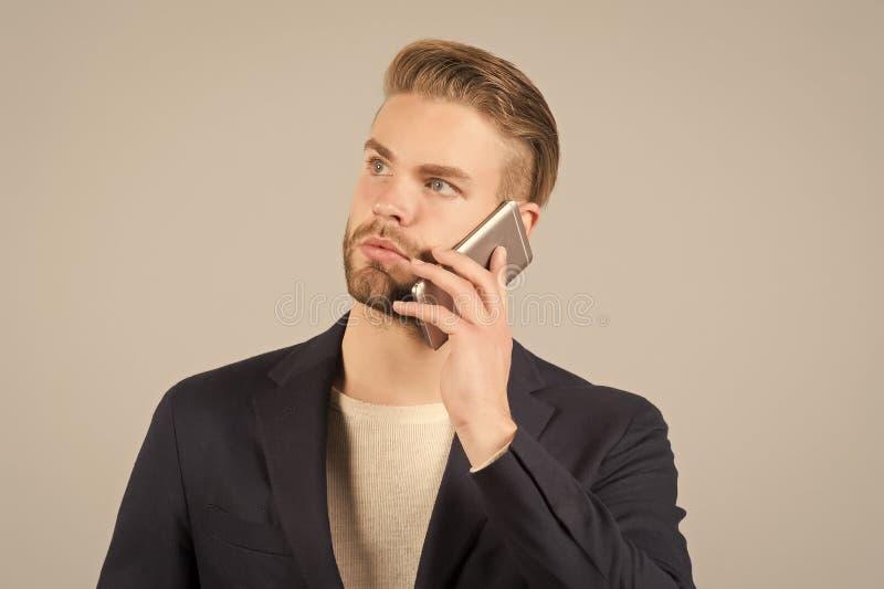Περιμένετε τη σύνδεση Το άτομο που καλλωπίζεται καλά μιλά το κινητό τηλεφωνικό γκρίζο υπόβαθρο Κινητό τηλέφωνο κλήσης επιχειρηματ στοκ εικόνα