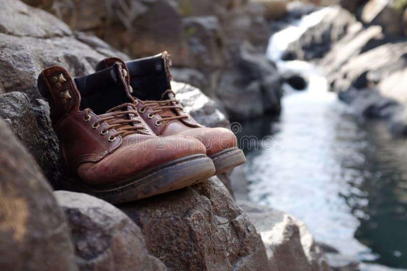 Περιορισμένες μπότες πεζοπορίας εστίασης παλαιές μπροστά από τον καταρράκτη στοκ εικόνα με δικαίωμα ελεύθερης χρήσης