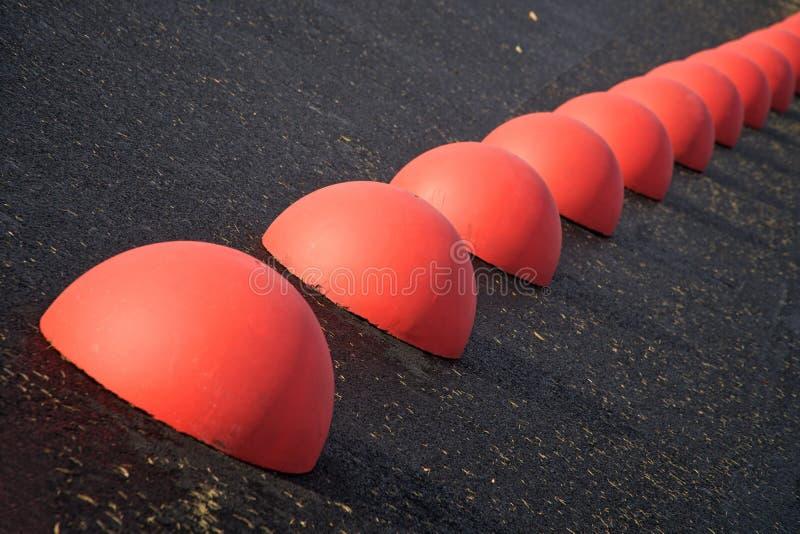 Περιοριστές χώρων στάθμευσης - κόκκινα συγκεκριμένα ημισφαίρια στην άσφαλτο στοκ εικόνες