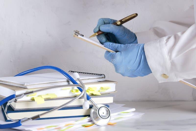 Περιοχή αποκομμάτων εκμετάλλευσης γιατρών και γράψιμο μιας συνταγής, σωρός των εγγράφων και των βιβλίων, στηθοσκόπιο στο άσπρο γρ στοκ φωτογραφία