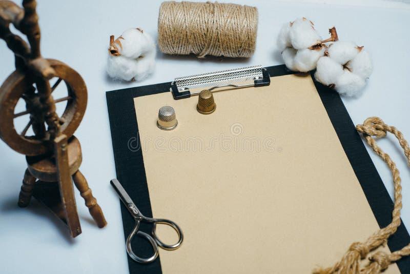 Περιοχή αποκομμάτων με το εκλεκτής ποιότητας έγγραφο, cottons σφαίρες και λίγη περιστρεφόμενη ρόδα Χλεύη κινηματογραφήσεων σε πρώ στοκ εικόνες
