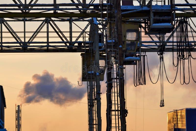 περιοχή βιομηχανική Υπαίθριο τρίποδο γερανών Ηλεκτρικός υπερυψωμένος διακινούμενος γερανός επάνω από την ανοικτή περιοχή αποθηκών στοκ φωτογραφία