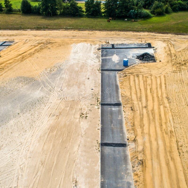 Περιοχή νέας κατασκευής από τον αέρα, λεπτομερής άποψη της ανάπτυξης μιας αδιέξοδης οδού, με την μπλε κινητή τουαλέτα για το cons στοκ εικόνες