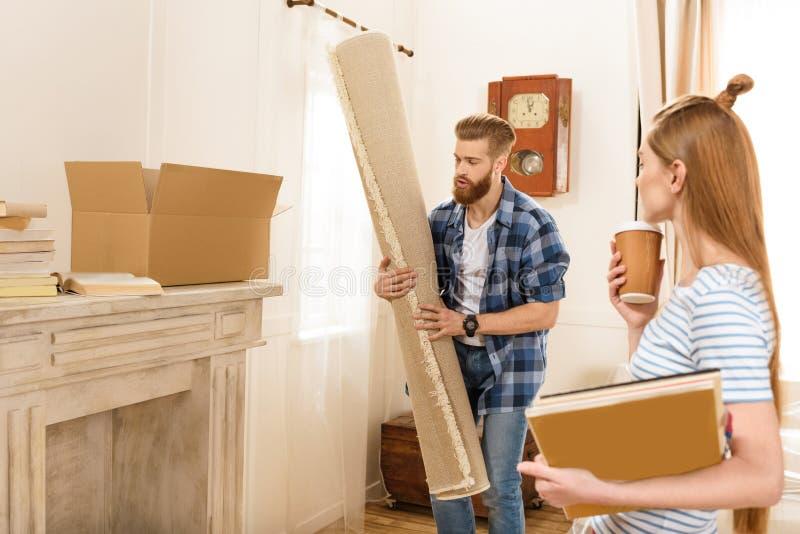 Περιοδικά και τάπητας εκμετάλλευσης ζεύγους κινούμενος στο καινούργιο σπίτι στοκ εικόνα με δικαίωμα ελεύθερης χρήσης