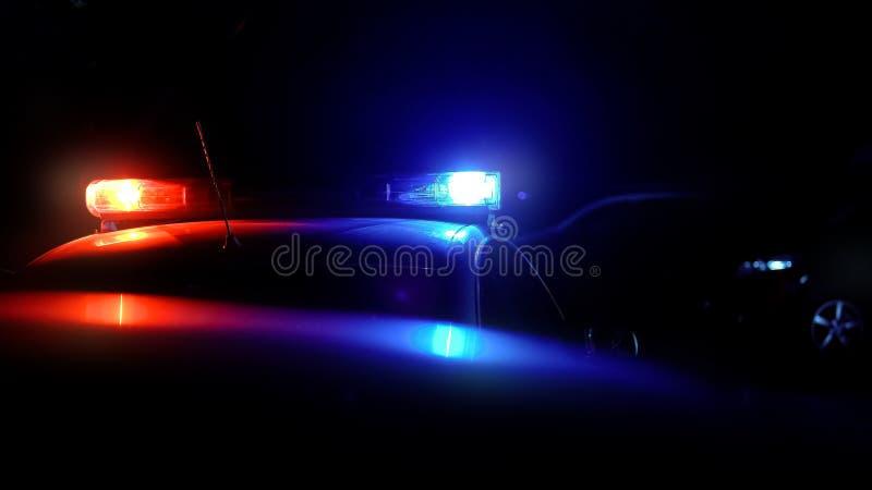 Περιπολικό αυτοκίνητο αστυνομίας με τους ηλεκτρικούς φακούς κατά τη διάρκεια της επιδρομής νύχτας ενάντια στο έγκλημα στην οδό στοκ εικόνες
