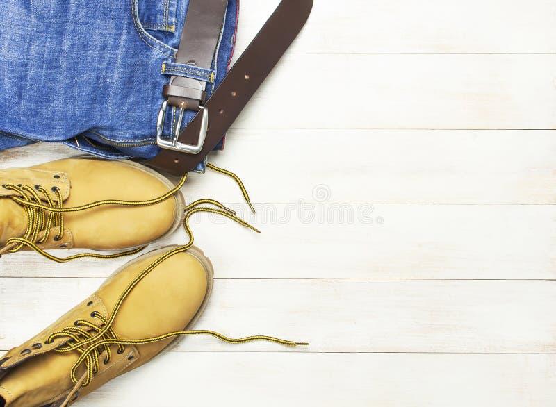 Περιστασιακή ένδυση ατόμων, κίτρινες μπότες εργασίας από το φυσικό δέρμα nubuck, τζιν παντελόνι και καφετιά ζώνη στην ξύλινη άσπρ στοκ φωτογραφίες