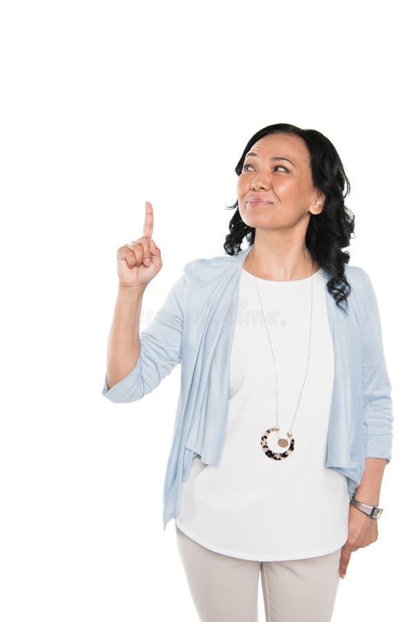 Περιστασιακή ασιατική γυναίκα που δείχνει με το δάχτυλο που απομονώνεται στο λευκό στοκ φωτογραφίες