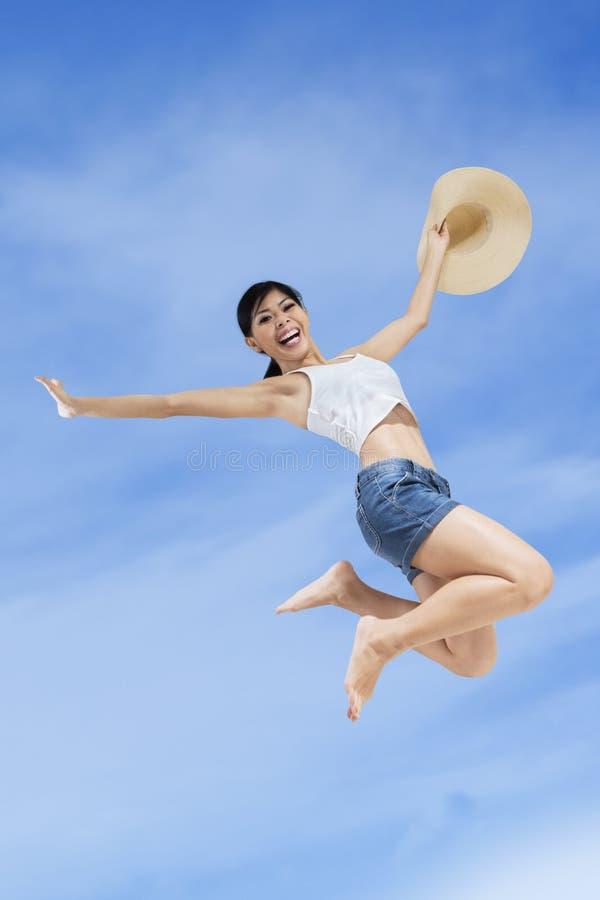Περιστασιακή γυναίκα που πηδά στον ουρανό στοκ φωτογραφία
