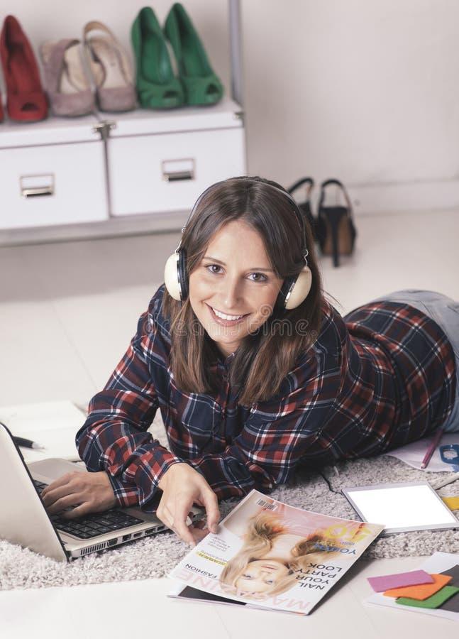 Περιστασιακή γυναίκα blogger που εργάζεται με το lap-top και το περιοδικό στο γραφείο μόδας της. στοκ φωτογραφία
