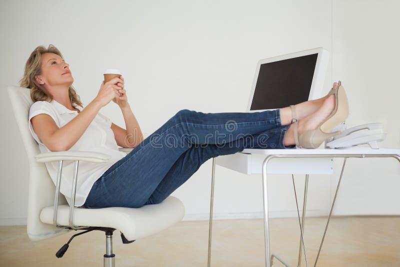Περιστασιακή επιχειρηματίας που έχει έναν καφέ με τα πόδια της επάνω στο γραφείο στοκ εικόνες