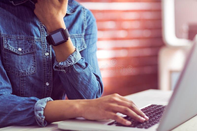 Περιστασιακή επιχειρηματίας που χρησιμοποιεί το lap-top και smartwatch στοκ φωτογραφία με δικαίωμα ελεύθερης χρήσης