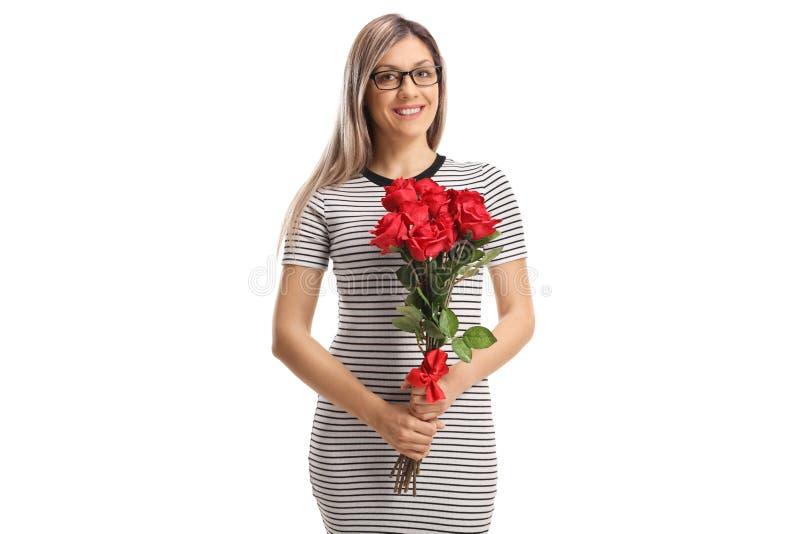 Περιστασιακή ευτυχής νέα γυναίκα που κρατά μια ανθοδέσμη των κόκκινων τριαντάφυλλων στοκ εικόνα