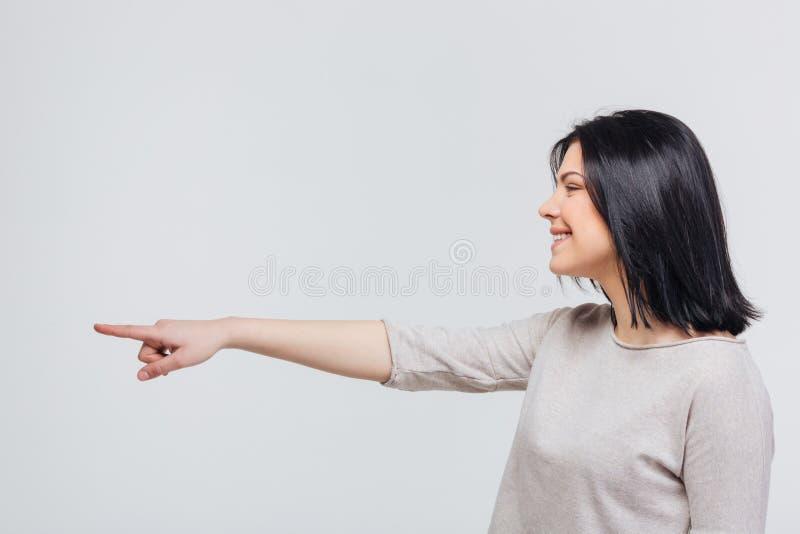 Περιστασιακή νέα γυναίκα που δείχνει το δάχτυλο κατά μέρος στοκ φωτογραφία