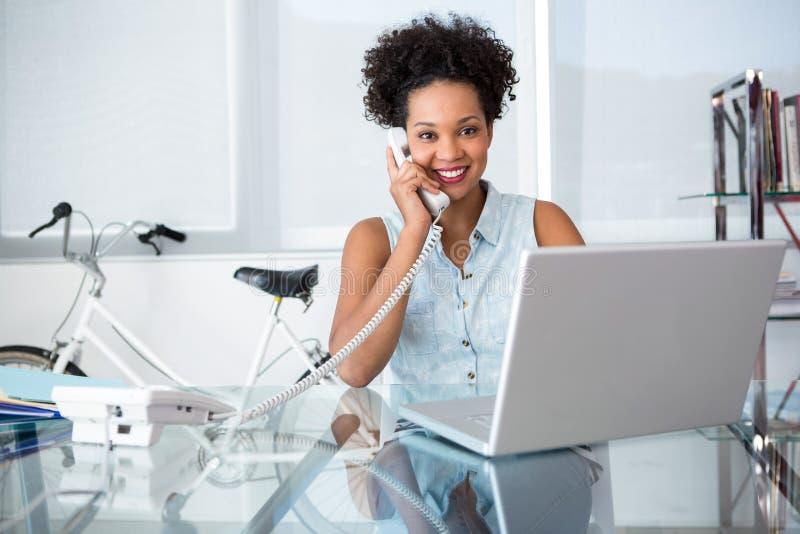 Περιστασιακή νέα γυναίκα που χρησιμοποιεί το τηλέφωνο και το lap-top στοκ εικόνες