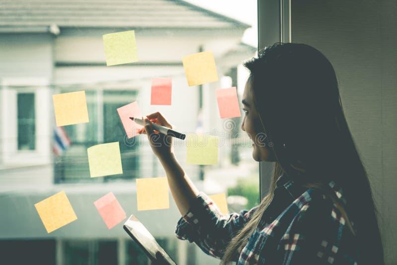 Περιστασιακοί δημιουργικοί ιδανικό και στόχος γραψίματος επιχειρησιακών γυναικών προς τα παράθυρα στοκ εικόνα