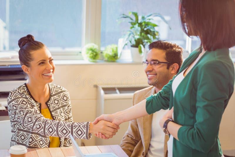 Περιστασιακοί επιχειρηματίες που τινάζουν τα χέρια στο γραφείο και το χαμόγελο στοκ φωτογραφία