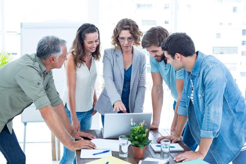 Περιστασιακοί συνάδελφοι που χρησιμοποιούν το lap-top στο γραφείο στοκ εικόνα με δικαίωμα ελεύθερης χρήσης
