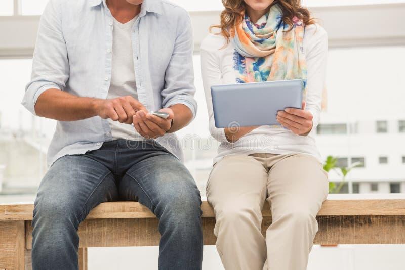 Περιστασιακοί σχεδιαστές που κάθονται στο ξύλινο γραφείο και που χρησιμοποιούν τις συσκευές στοκ εικόνες