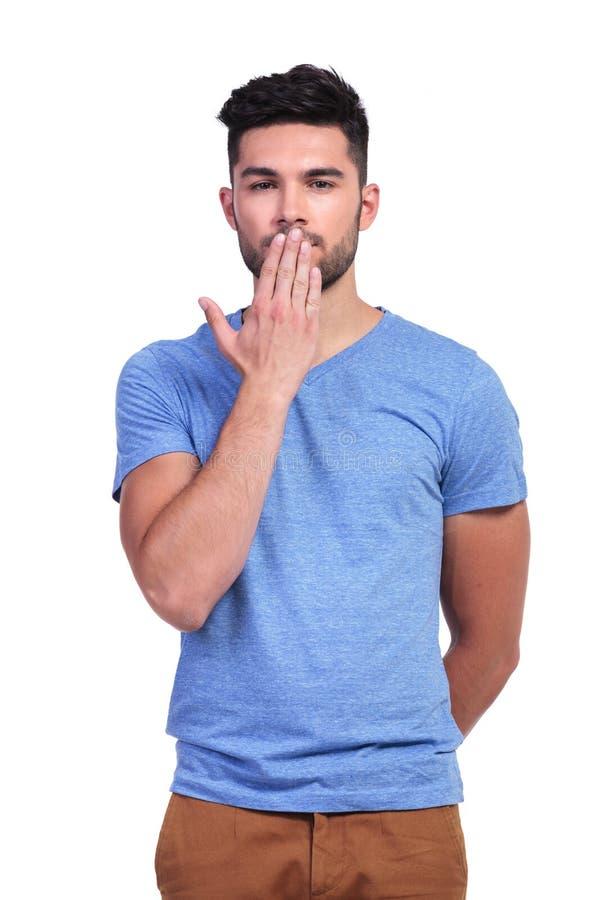 Περιστασιακός νεαρός άνδρας που καλύπτει το στόμα του στοκ εικόνα