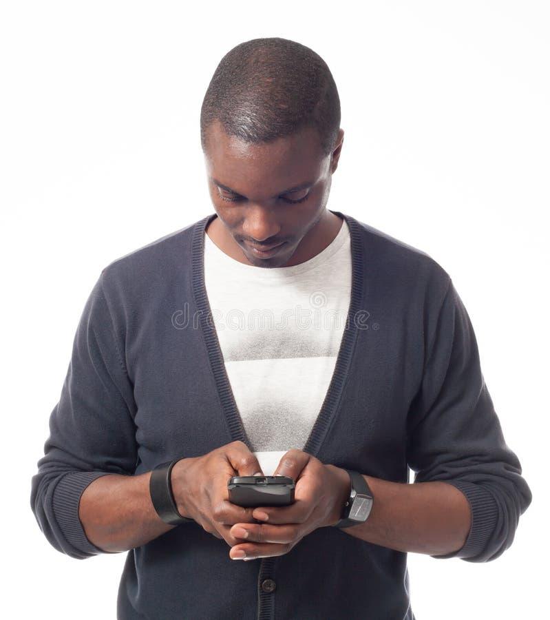 Περιστασιακός ντυμένος μαύρος που φαίνεται το κινητό τηλέφωνό του στοκ φωτογραφία με δικαίωμα ελεύθερης χρήσης