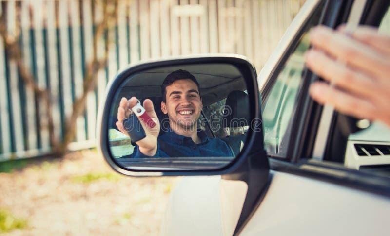 Περιστασιακός οδηγός τύπων που παρουσιάζει κλειδιά αυτοκινήτων στην αντανάκλαση καθρεφτών πλάγιας όψης Ο επιτυχής νεαρός άνδρας α στοκ φωτογραφία με δικαίωμα ελεύθερης χρήσης