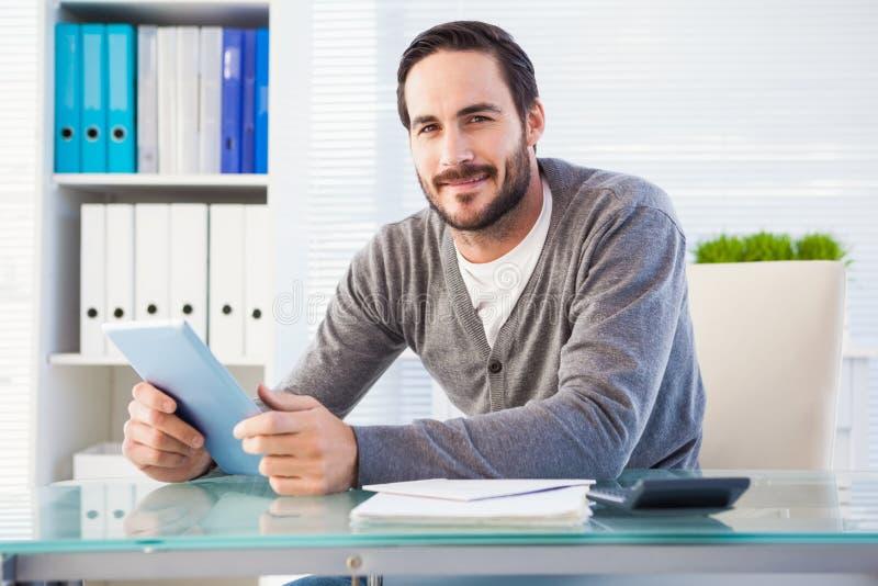 Περιστασιακός χαμογελώντας επιχειρηματίας που χρησιμοποιεί την ταμπλέτα και τον υπολογιστή στοκ φωτογραφία με δικαίωμα ελεύθερης χρήσης