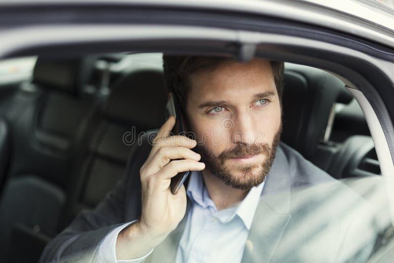 Περιστασιακό επιχειρησιακό άτομο στο κινητό τηλέφωνο στο οπίσθιο τμήμα του αυτοκινήτου στοκ εικόνα με δικαίωμα ελεύθερης χρήσης