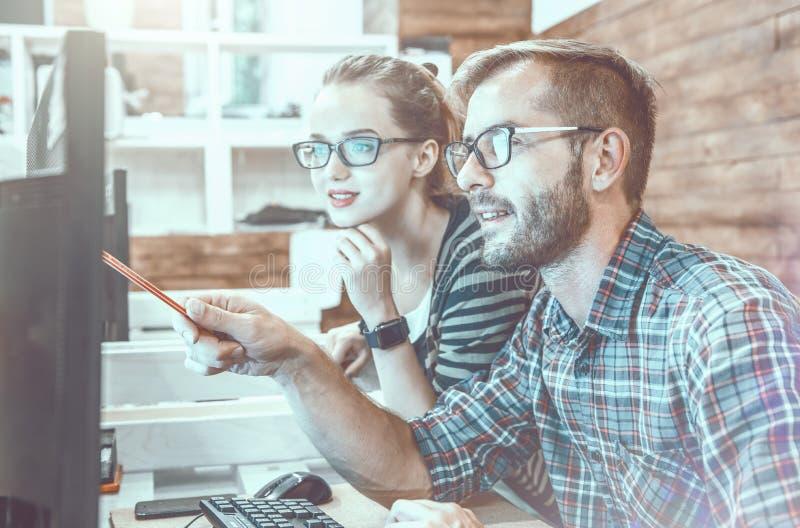 Περιστασιακό επιχειρησιακό ζεύγος που χρησιμοποιεί τον υπολογιστή στο γραφείο Δύο συνάδελφοι που εργάζονται μαζί σε ένα καινοτόμο στοκ φωτογραφίες με δικαίωμα ελεύθερης χρήσης