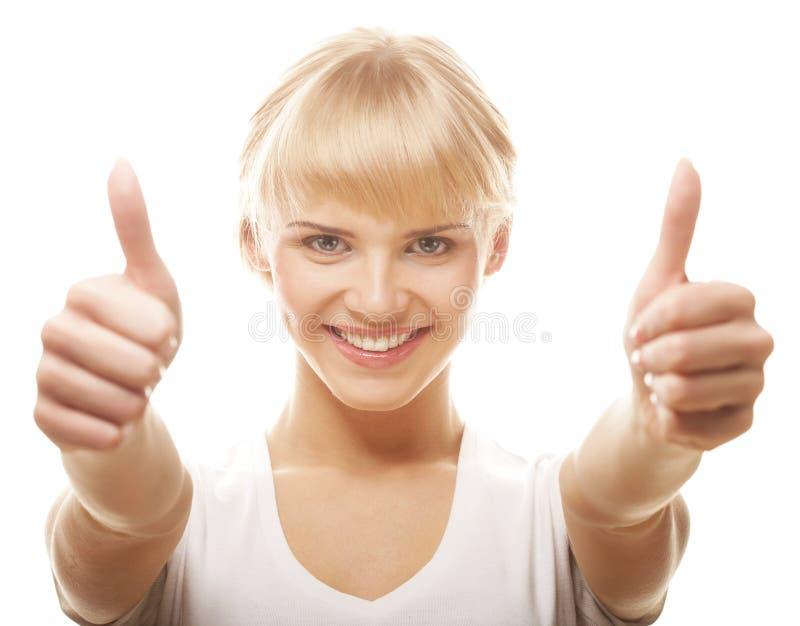 Περιστασιακό κορίτσι που παρουσιάζει αντίχειρες και που χαμογελά στοκ εικόνα
