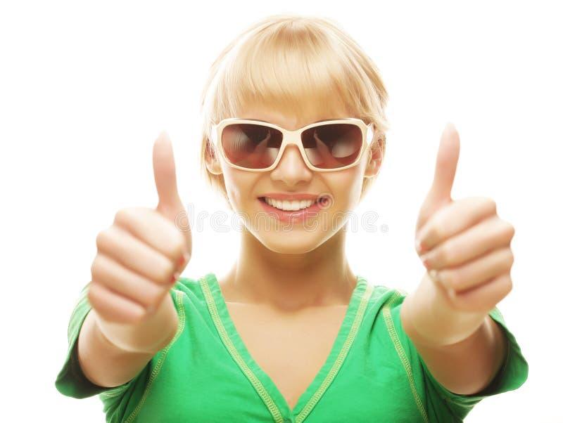 Περιστασιακό κορίτσι που παρουσιάζει αντίχειρες και που χαμογελά στοκ φωτογραφία με δικαίωμα ελεύθερης χρήσης
