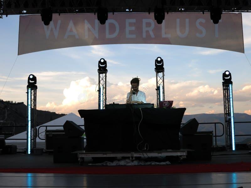 Περιστροφές του DJ Drez στη σκηνή κατά τη διάρκεια της συναυλίας με το τοπίο βουνών στοκ φωτογραφία