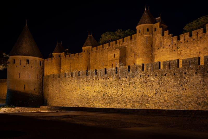 Περιτοιχισμένη πόλη Carcasone κατά τη διάρκεια της έναρξης της νύχτας Άποψη του εξωτερικού τοίχου xon οι αμυντικοί πύργοι του στοκ εικόνα