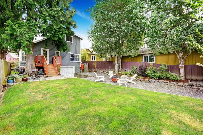 Περιφραγμένη πίσω αυλή με την περιοχή patio και τις άσπρες καρέκλες adirondack στοκ φωτογραφία με δικαίωμα ελεύθερης χρήσης