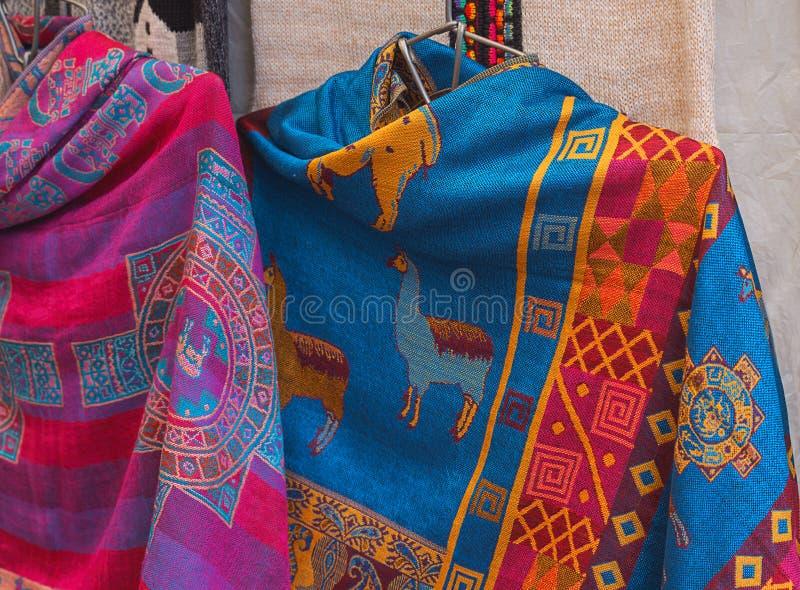 Περουβιανό θηλυκό ζωηρόχρωμο poncho φορεμάτων με llama μορφής στην αγορά Machu Picchu μια από τη νέα κατάπληξη επτά του κόσμου, C στοκ εικόνες