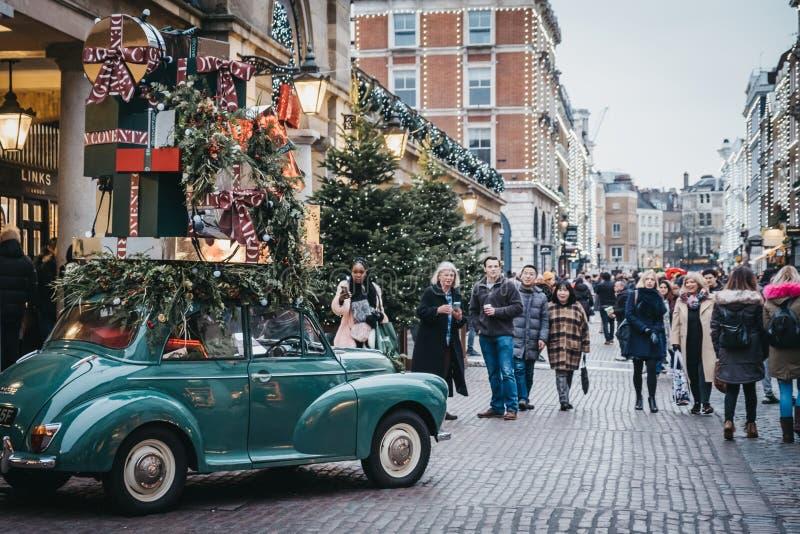 Περπάτημα ανθρώπων προηγούμενο και λήψη των φωτογραφιών των διακοσμήσεων αυτοκινήτων Χριστουγέννων στην αγορά κήπων Covent, Λονδί στοκ εικόνες