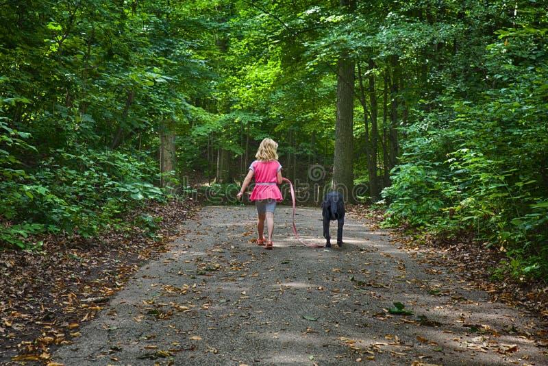 περπάτημα σκυλιών παιδιών στοκ φωτογραφίες