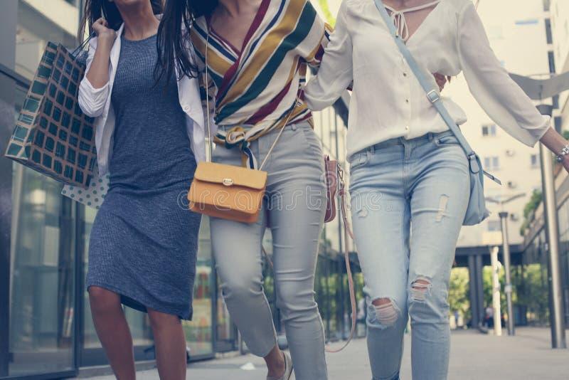 Περπάτημα τριών νέων κοριτσιών ευχαριστημένο από τις τσάντες αγορών στοκ φωτογραφίες
